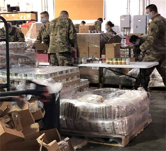 Members of the National Guard pack food at the Emergency Food Network warehouse
