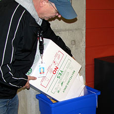 Man emptying box contents into recycling bin