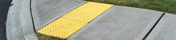 Yellow Ramp on Sidewalk Surrounded by Grass