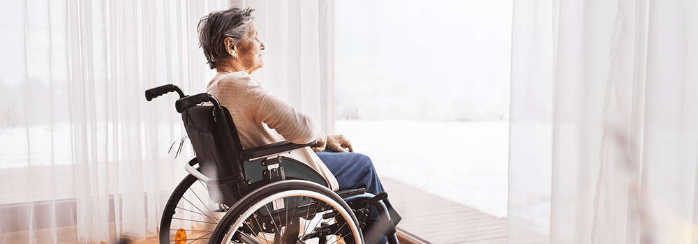 photo of a senior woman in a wheelchair looking out a window